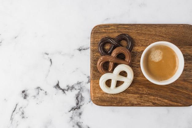 Ciambelline salate e tazza di caffè del cioccolato sul tagliere sopra fondo strutturato di marmo Foto Gratuite