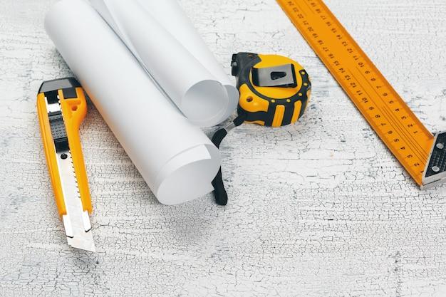 Cianografie architettoniche e rotoli di cianografia e strumenti di disegno sul piano di lavoro. Foto Premium