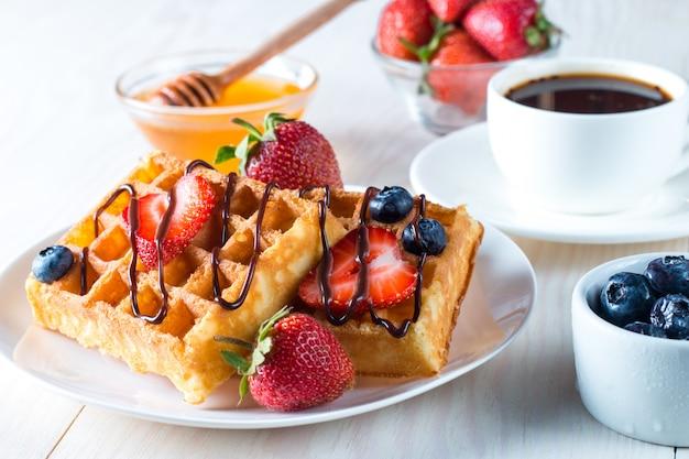 Cibi freschi fatti in casa di waffle belgi ai frutti di bosco con miele, cioccolato, fragola, mirtillo, sciroppo d'acero e crema. concetto sano della prima colazione del dessert con succo Foto Premium
