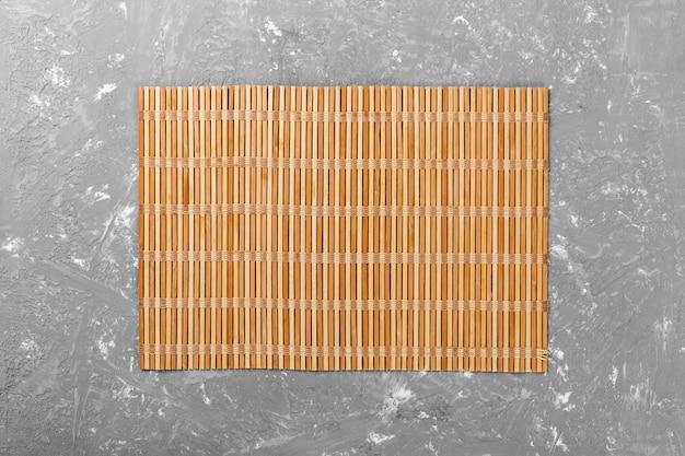 Cibo asiatico vuoto. stuoia di bambù marrone sulla vista superiore del fondo di legno con la disposizione del piano del copyspace Foto Premium