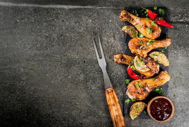 Cibo estivo. idee per barbecue, grigliate. cosce di pollo, ali grigliate, fritte sul fuoco. con peperoncino piccante, salsa al limone e barbecue. tavolo in pietra scura. copia spazio vista dall'alto Foto Premium