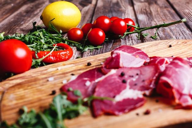 Cibo fresco e sano la carne rossa affettata si trova sulla tavola di legno con la rucola Foto Gratuite