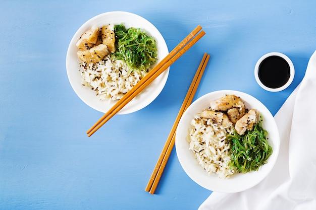 Cibo giapponese. ciotola di riso, pesce bianco bollito e wakame chuka o insalata di alghe. vista dall'alto. disteso Foto Gratuite