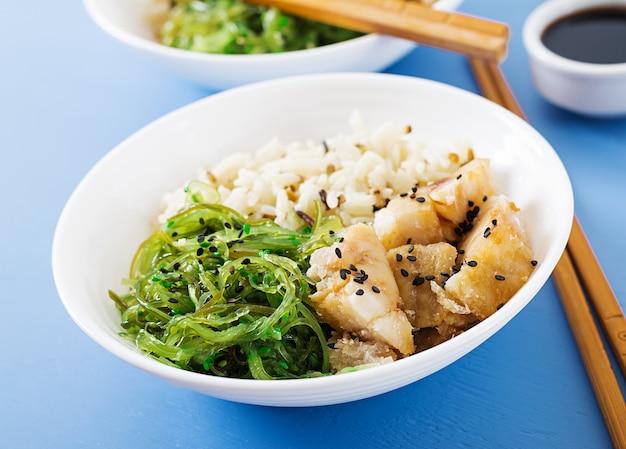Cibo giapponese. ciotola di riso, pesce bianco bollito e wakame chuka o insalata di alghe. Foto Gratuite