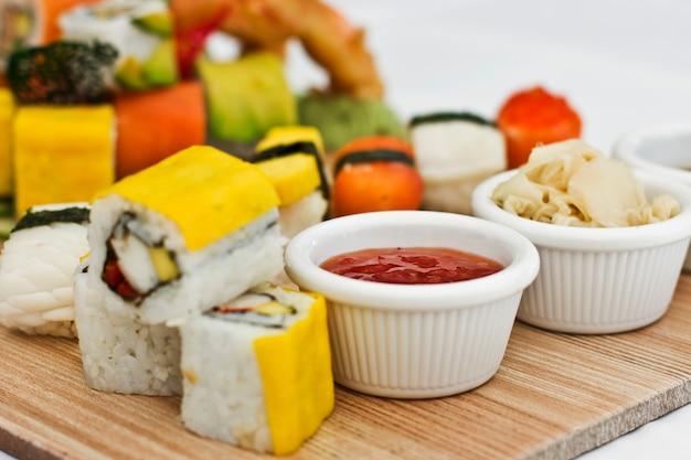 Cibo giapponese - sushi, sashimi, rotoli su una tavola di legno. isolato Foto Premium