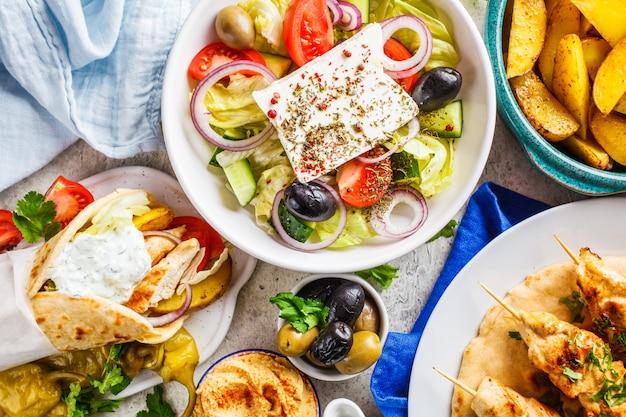 Cibo greco: insalata greca, pollo souvlaki, gyros e spicchi di patate al forno su sfondo grigio, vista dall'alto. concetto di cucina tradizionale greca. Foto Premium