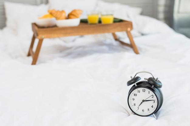 Tavoli Per Colazione A Letto : Cibo gustoso sul tavolo della colazione e sveglia sul letto