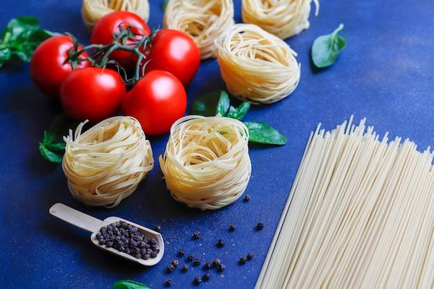 Cibo italiano . cucina italiana. ingredienti pomodori, pomodorini gialli, basilico fresco, semi di pepe nero, pasta varia. Foto Gratuite