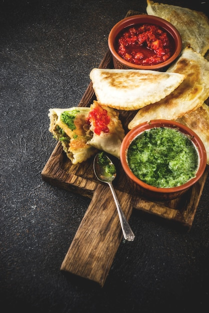 Cibo latino americano, messicano, cileno. empanadas di pasticceria tradizionale al forno con carne di manzo, due salse piccanti Foto Premium