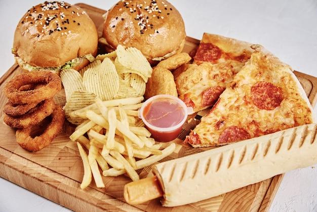 Cibo malsano e spazzatura. tipi differenti di alimenti a rapida preparazione sulla tavola, primo piano Foto Premium