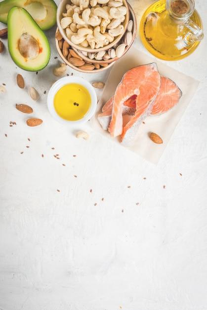 Cibo salutare. prodotti con grassi sani. omega 3, omega 6. ingredienti e prodotti: trota (salmone), olio di semi di lino, avocado, mandorle, anacardi, pistacchi. su un tavolo di pietra bianca. vista dall'alto di copyspace Foto Premium