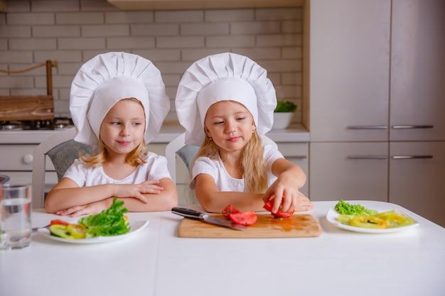 Cibo sano a casa. famiglia felice in cucina. due simpatici bambini divertenti stanno preparando le verdure. Foto Premium