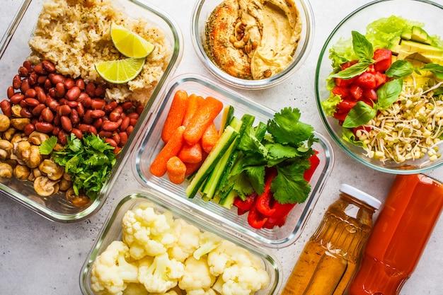 Cibo sano vegano in contenitori di vetro, vista dall'alto. riso, fagioli, verdure, hummus e succo. Foto Premium