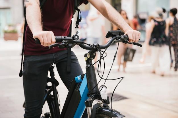 Ciclista che guida l'e-bike attraverso la città Foto Gratuite