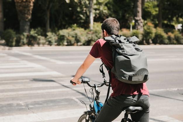 Ciclista di vista posteriore che aspetta al passaggio pedonale Foto Gratuite