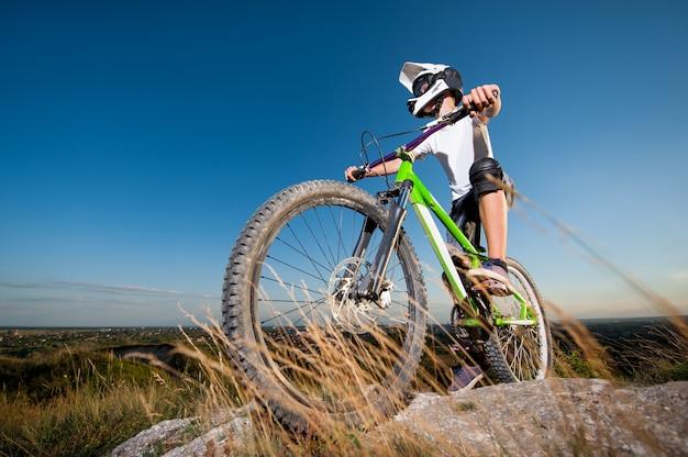 Ciclista si prepara a guidare in discesa in mountain bike Foto Premium