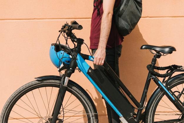 Ciclista urbano che sta accanto all'e-bici Foto Gratuite