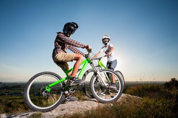 Ciclisti con mountain bike sulla collina sotto il cielo blu Foto Premium