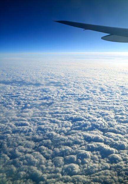 Cielo blu profondo e nuvole bianche pure con l'ala dell'aeroplano veduta dall'aereo durante il volo Foto Premium