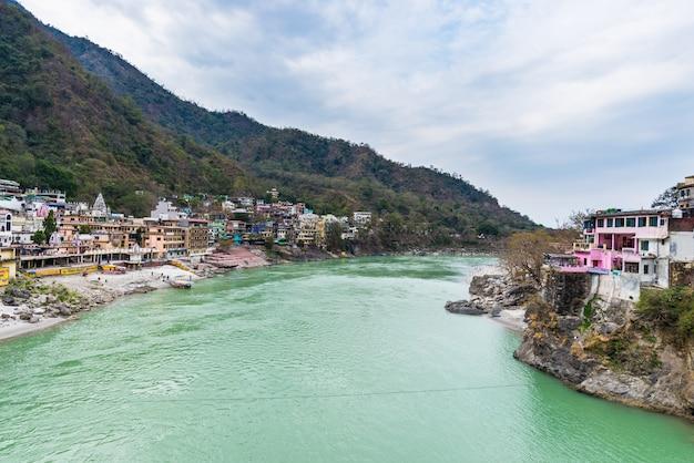 Cielo drammatico a rishikesh, città santa e destinazione del viaggio in india. cielo colorato e nuvole che riflettono sul fiume gange. Foto Premium