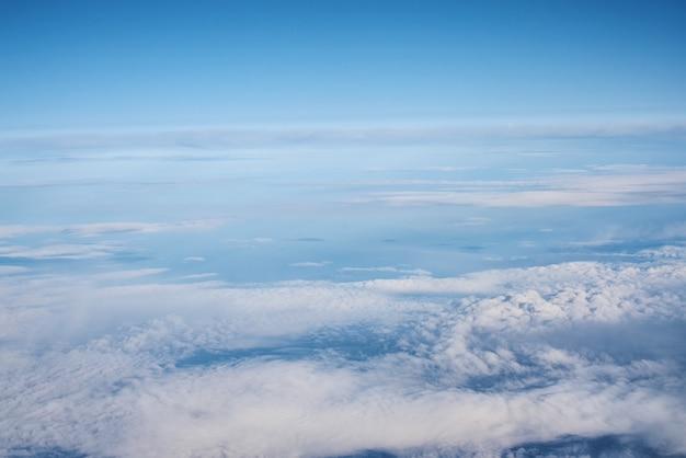 Cielo nuvoloso blu, vista dal finestrino dell'aereo. vista aerea di cloudscape Foto Premium