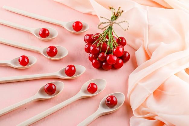 Ciliege in cucchiai di legno sullo spazio del tessuto e di rosa, vista dell'angolo alto. Foto Gratuite