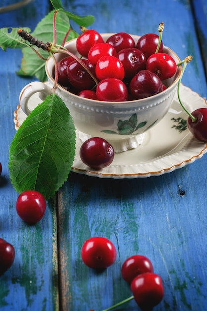 Ciliegie fresche in tazza da tè vintage Foto Premium