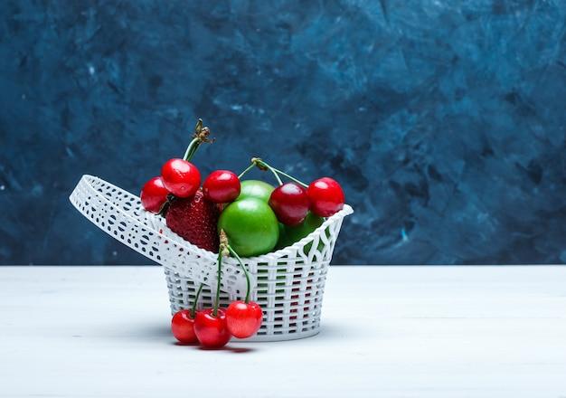 Ciliegie in un cestino con fragole e prugne verdi Foto Gratuite