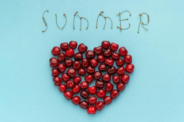 Ciliegie rosse a forma di cuore e testo estate Foto Premium