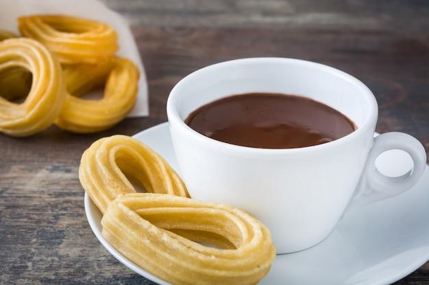 Cioccolata calda con churros sulla tavola di legno colazione spagnola Foto Premium