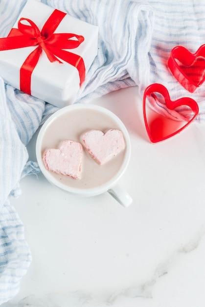 Cioccolata calda con marshmallow a forma di cuore, festa di san valentino, con formine per biscotti rosse e confezione regalo di san valentino copyspace vista dall'alto Foto Premium