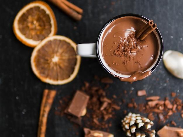 Cioccolata calda vicino a arance e dolci al cacao Foto Gratuite