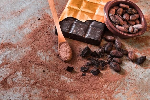Cioccolata spezzettata e ciotola di fave di cacao su fondo rustico Foto Gratuite