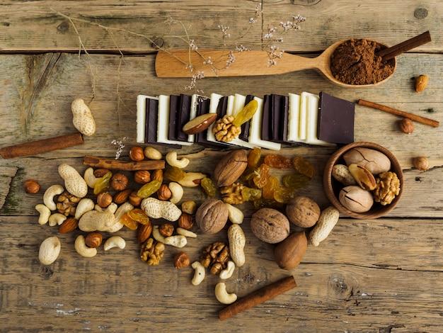 Cioccolatini diversi, noci e altri dolci su un tavolo di legno Foto Premium