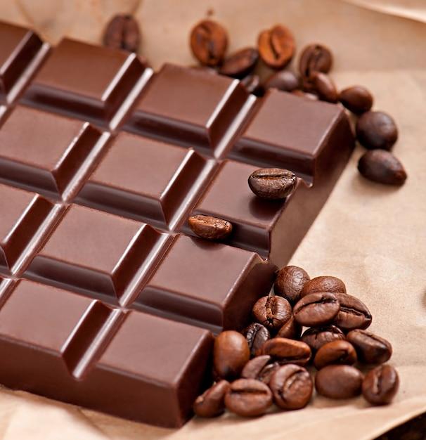 Cioccolato e chicchi di caffè su carta beige Foto Gratuite