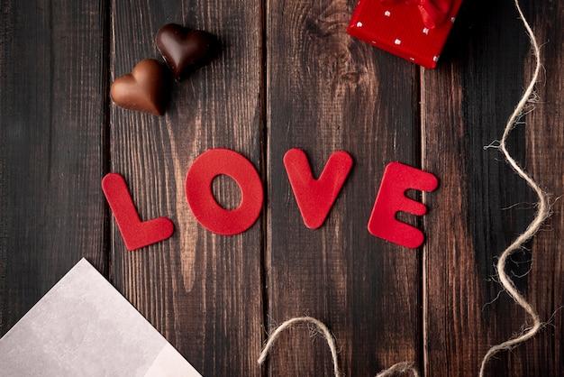 Cioccolato in forma di cuore su fondo di legno con amore Foto Gratuite