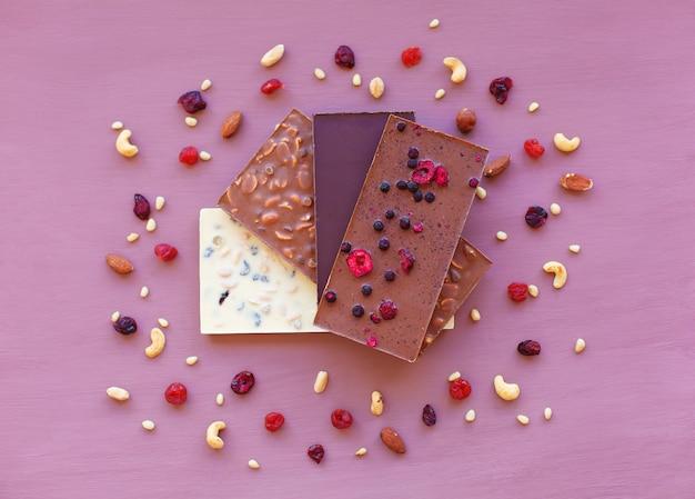Cioccolato su viola, circondato da noci e frutta secca. cioccolato. barretta di cioccolato. Foto Premium