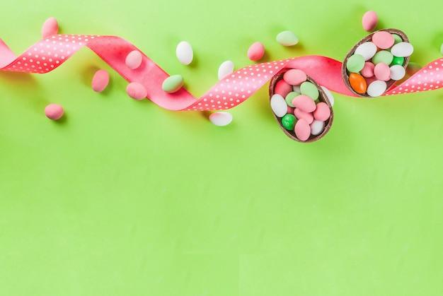 Cioccolato uovo di pasqua, uova di caramella, uova di quaglia e nastro festivo Foto Premium