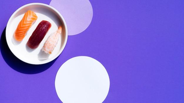 Ciotola bianca con sushi su uno sfondo blu con cerchi bianchi Foto Gratuite