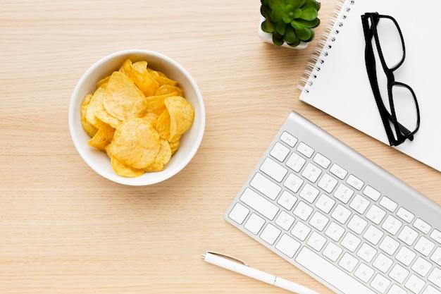 Ciotola con patatine fritte in ufficio Foto Gratuite