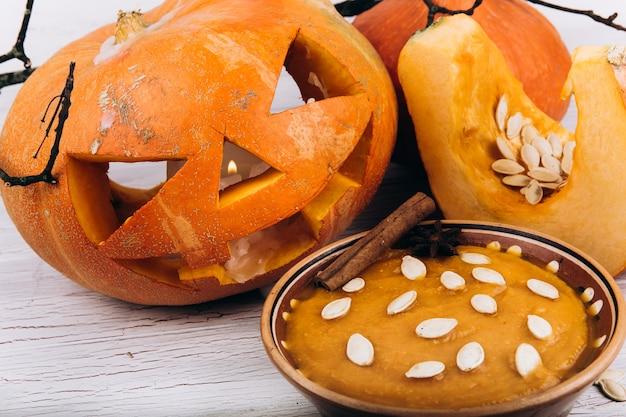 Ciotola con zuppa si trova prima di scarry zucca di halloween sul tavolo Foto Gratuite