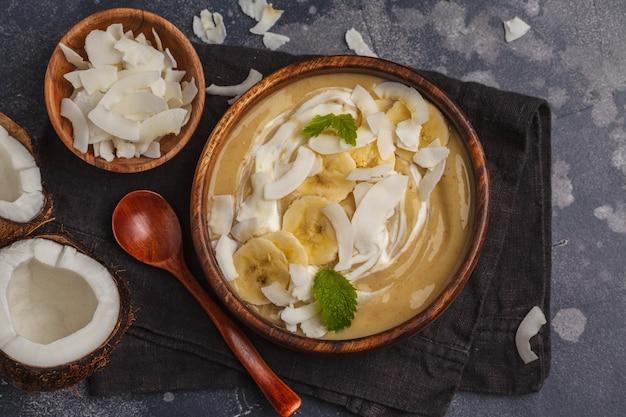 Ciotola del frullato della banana della noce di cocco in un piatto di legno su un fondo scuro, concetto sano dell'alimento del vegano. vista dall'alto, copia spazio. Foto Premium