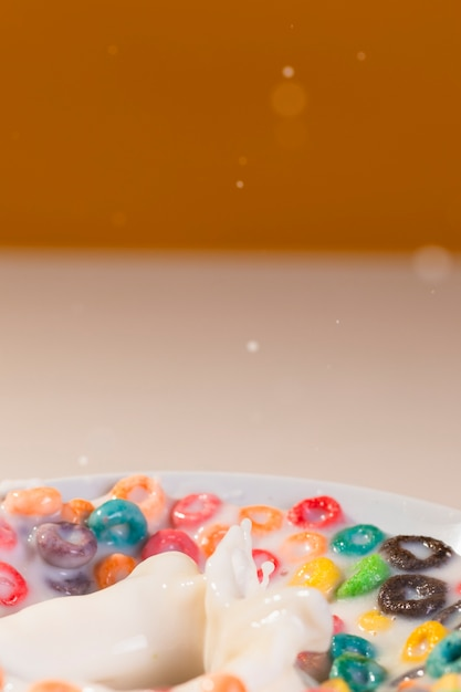 Ciotola del primo piano con cereali e latte sulla tavola Foto Gratuite
