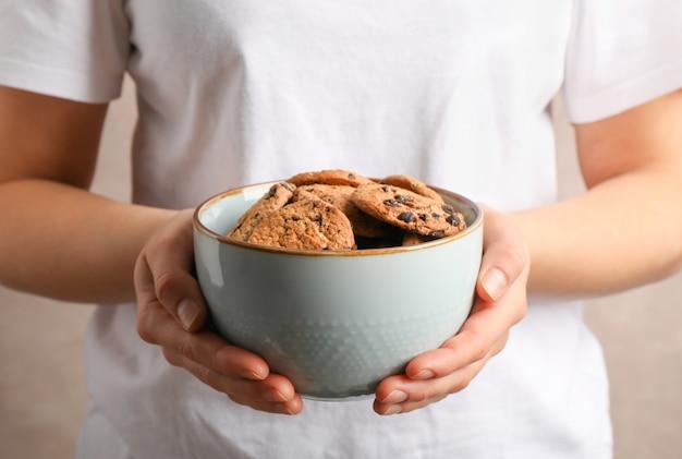 Ciotola della tenuta della donna con i biscotti di pepita di cioccolato saporiti, primo piano Foto Premium
