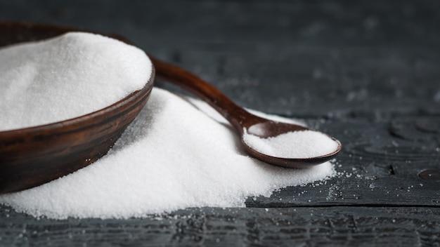 Ciotola di argilla con sale marino bianco e cucchiaio di legno sul tavolo. Foto Premium