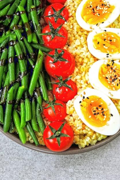 Ciotola di buddha con bulgur, fagiolini, pomodorini e metà dell'uovo sodo. cibo sano in una ciotola. il concetto di nutrizione dietetica. Foto Premium