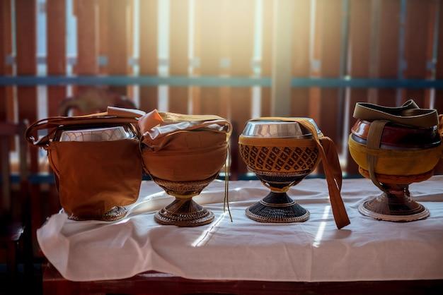 Ciotola di elemosina del monaco sul tavolo con illuminazione. Foto Premium