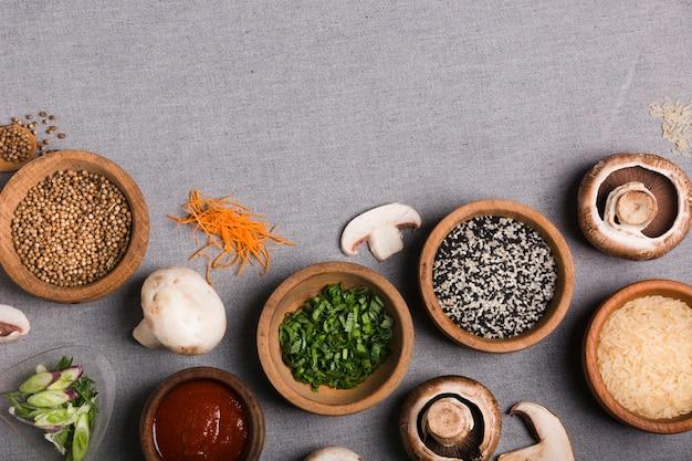 Ciotola di erba cipollina in legno; semi di coriandolo; salsa; fungo; chicchi di riso e carota grattugiata sulla tovaglia di lino grigio Foto Gratuite
