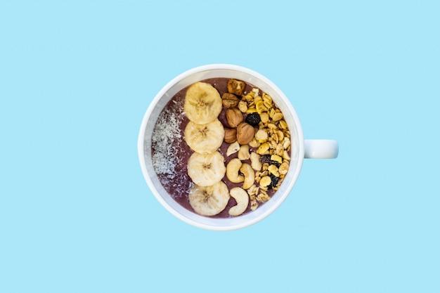 Ciotola di frullato di frutta con noci e banana, vista dall'alto. lay piatto di una ciotola di acai con cereali, anacardi e nocciole in superficie blu brillante Foto Premium