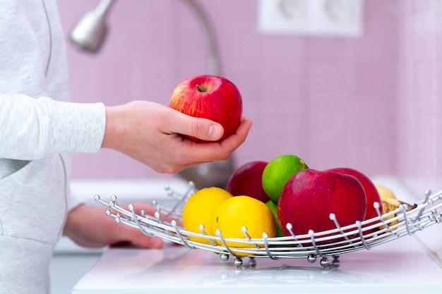 Ciotola di frutta matura fresca sulla tavola in cucina a casa. vitamine, prodotti biologici ecologici per merenda sana. cibo pulito, corretta alimentazione. dieta Foto Premium